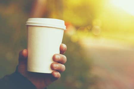 tazza di th�: mano che tiene bicchiere di carta di caff� su sfondo naturale mattina