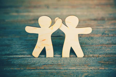 team working: Wooden little men holding hands on wooden boards background. Symbol of friendship, love and teamwork Stock Photo