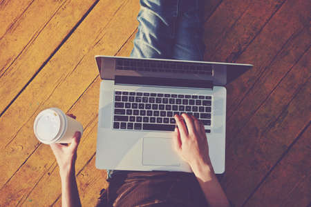 keyboard: Laptop and paper cup of coffee in girls hands sitting on a wooden floor