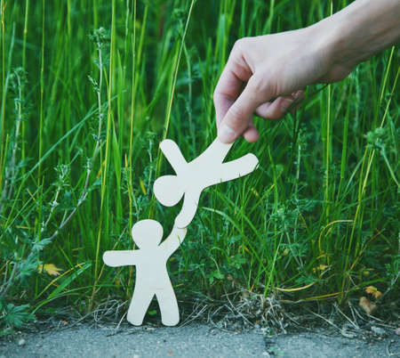 Wooden little men holding hands in natural grass with help of human hand. Symbol of friendship, love, teamwork or assistance concept