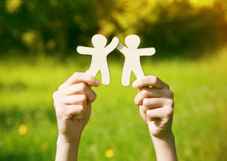 join hands: Hands holding wooden little men on natural background. Symbol of friendship, love, teamwork or ecology concept Stock Photo