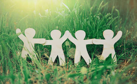 Wooden little men holding hands in summer grass. Symbol of friendship, family, teamwork or ecology concept Stockfoto