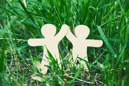 amistad: Pequeños hombres de madera de la mano en la hierba natural. Símbolo de la amistad, el amor, el trabajo en equipo o el concepto de la ecología Foto de archivo
