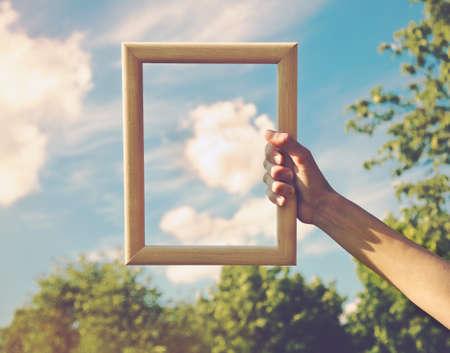 Hand die een houten frame op wolkachtergrond houdt. Zorg, veiligheid, geheugen of schilderkunst. Stockfoto