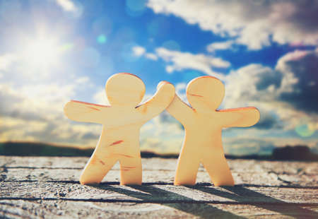 Wooden little men holding hands on sky and sun background. Symbol of friendship, love and teamwork Stock Photo