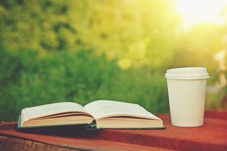 paper cup of coffee and book in the green grass in summer sunlight park