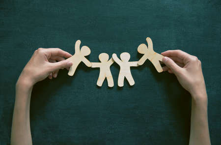 Wooden little men holding hands on blackboard background. Symbol of friendship, love or teamwork concept