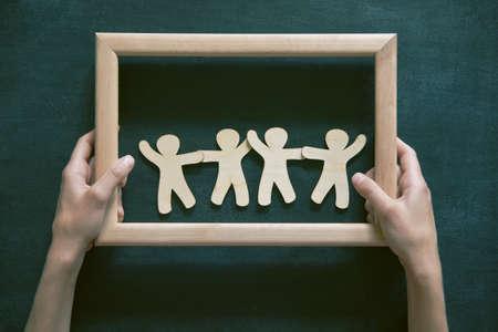 caja fuerte: Pequeños hombres de madera de la mano en el marco en el fondo pizarra. Símbolo de la amistad, la seguridad o el trabajo en equipo concepto