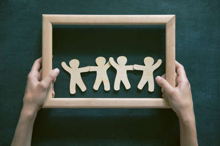 Wooden little men holding hands in frame on blackboard background. Symbol of friendship, safeness or teamwork concept