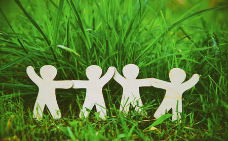 Wooden little men holding hands in summer grass. Symbol of friendship, family, teamwork or ecology concept Foto de archivo
