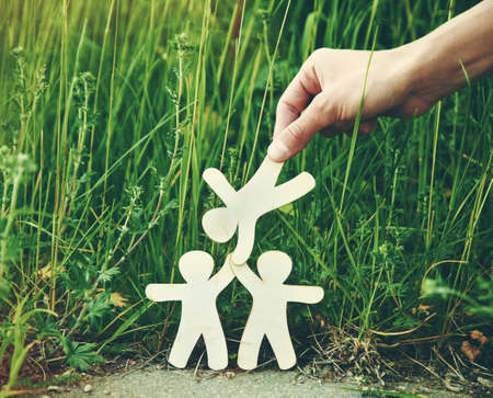 Wooden little men holding hands in natural grass. Symbol of friendship, love, teamwork or ecology concept