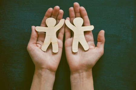 Handen houden van kleine houten mannen op bord achtergrond. Symbool van vriendschap, liefde of teamwork concept Stockfoto
