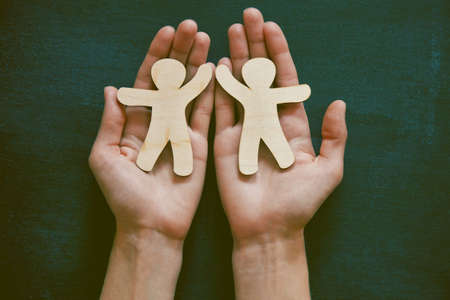 hand in hand: Hands holding little wooden men on blackboard background. Symbol of friendship, love or teamwork concept