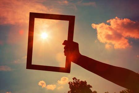 手拿著日出天空背景上的木製框架。保健,安全,存儲或繪畫的概念。