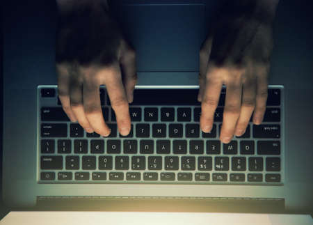 hands with laptop above typing in night