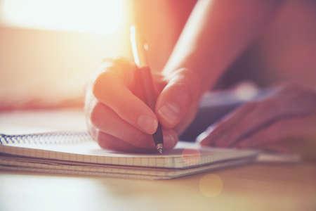persona escribiendo: manos de una mujer con l�piz de escribir en el cuaderno