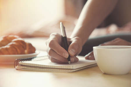writing desk: female hands with pen writing on notebook with morning coffee and croissant