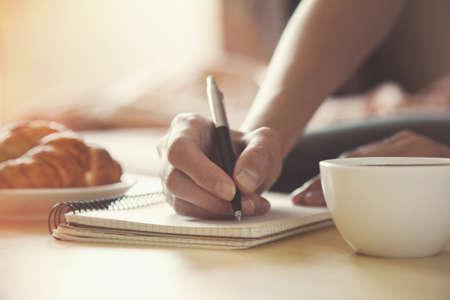 persona escribiendo: manos femeninas con pluma de escribir en el cuaderno con caf� de la ma�ana y un croissant
