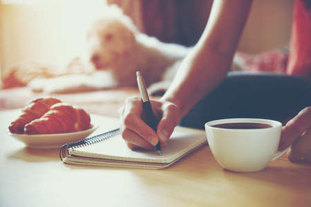 female hands with pen writing on notebook with morning coffee and croissant