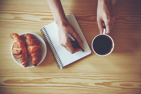 person writing: Hands with pen writing on notebook with morning coffee and croissant. View from above