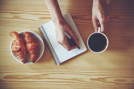 papier lettre: Mains avec stylo �criture sur ordinateur portable avec le caf� du matin et un croissant. Vue du dessus