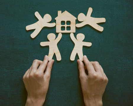 Hands holding little wooden men and house on blackboard background. Symbol of construction, sweet home concept Banco de Imagens