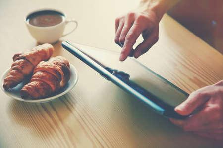 手中拿著用早晨咖啡和羊角麵包數字平板電腦。