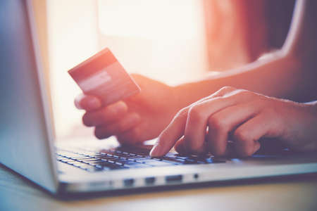pagando: Manos que sostienen la tarjeta de crédito y usando la computadora portátil. Las compras en línea