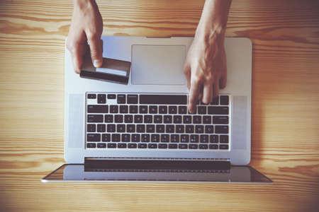 tarjeta de credito: Manos que sostienen la tarjeta de cr�dito y usando la computadora port�til. Vista desde arriba Foto de archivo