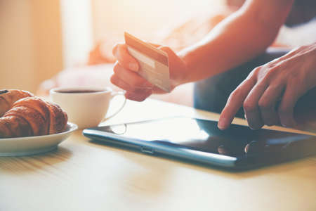 Hands holding credit card and using digital tablet pc with morning coffee and croissant. Online shopping. Stock Photo