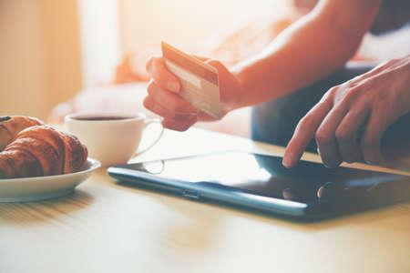 pagando: Manos que sostienen la tarjeta de crédito y que usa la PC de la tableta digital con café de la mañana y un croissant. Las compras en línea.