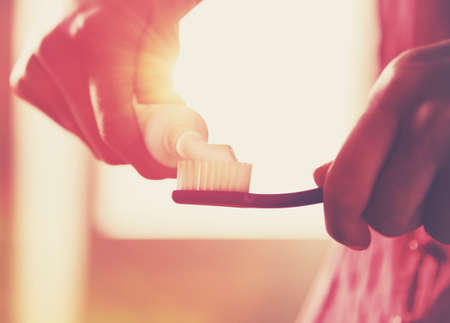 morning routine: Hands holding a toothbrush and placing toothpaste on it in morning sunrise