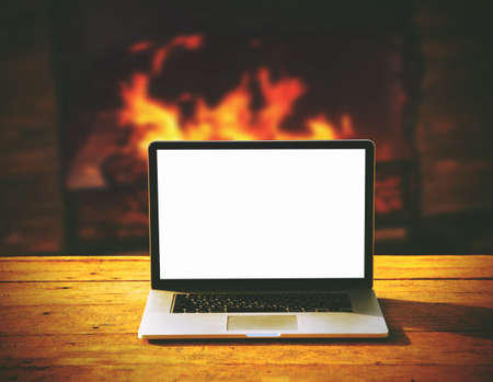 hearth and home: laptop with blank screen for copyspace on wooden table on fireplace background