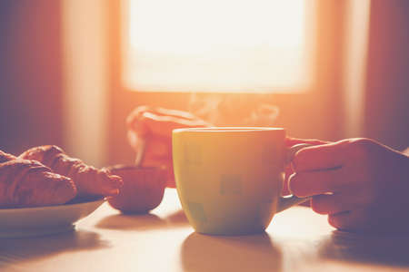frisches Frühstück mit heißem Kaffee und Croissant in Morgensonnenlicht