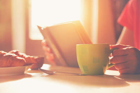morning coffee: fresh breakfast with hot coffee and reading book in morning sunlight