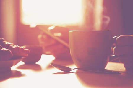 desayuno: desayuno fresco con caf� caliente y el tel�fono inteligente de navegaci�n en la ma�ana la luz del sol Foto de archivo