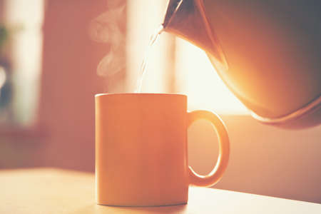 copa: hervidor de agua vertiendo agua hirviendo en una taza en la mañana la luz del sol