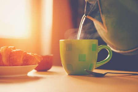 calor: hervidor de agua vertiendo agua hirviendo en una taza durante el desayuno en la mañana la luz del sol Foto de archivo