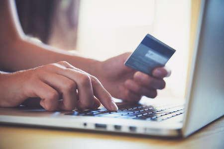 klawiatury: Ręce trzyma karty kredytowej i przy użyciu komputera przenośnego. Zakupy online