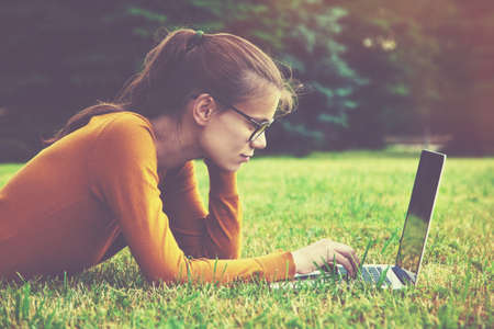 Smiling girl with glasses lying on the grass and using laptop and typing