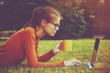 wireless woman work working: girl lying on the grass and using laptop and typing with coffee or tea mug