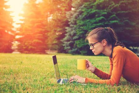 소녀 잔디에 누워 노트북을 사용하고 커피 또는 홍차 잔 입력. 복사 공간 스톡 콘텐츠