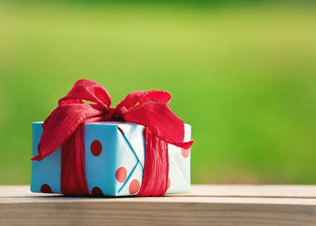 PRESENT: gift box on wooden table on natural sunny background