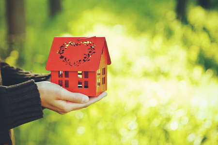 hands holding red model of house as symbol on natural garden background