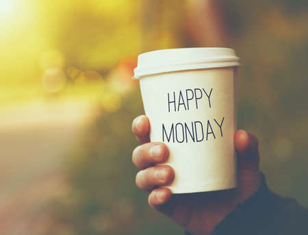 morning coffee: hand holding paper cup of coffee with Happy Monday motivational text on natural morning background