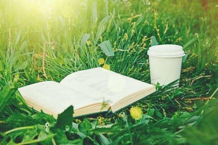 여름 햇빛 공원에서 푸른 잔디에서 커피와 책의 종이 컵 스톡 콘텐츠