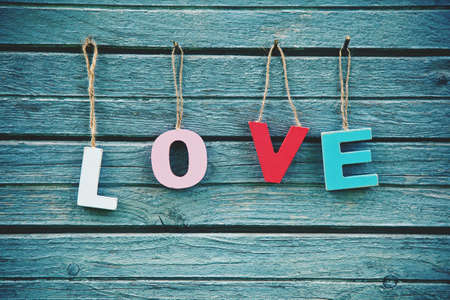 natural love: The word Love with wooden multi colored letters on natural board background
