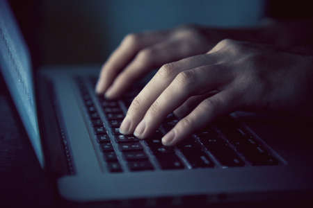 hands with laptop typing in night Banque d'images