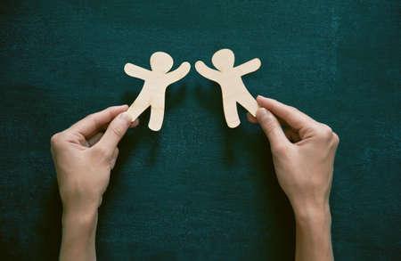 amicizia: Mani in possesso di piccoli uomini di legno su sfondo lavagna. Simbolo di amicizia, amore o concetto di squadra