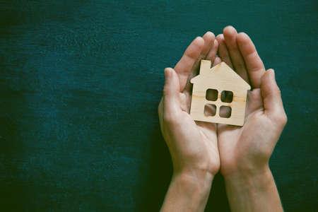 caja fuerte: Manos que sostienen la pequeña casa de madera en el fondo de la pizarra. Símbolo de la construcción, la seguridad o el concepto de hogar dulce